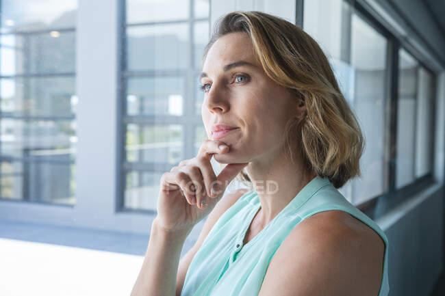 Розумно одягнена кавказька жіноча бізнес-творчість з білявим волоссям, дивлячись у вікно мислення, з рукою на підборіддя. Творчий бізнес-професіонал, який працює в сучасному офісі.. — стокове фото