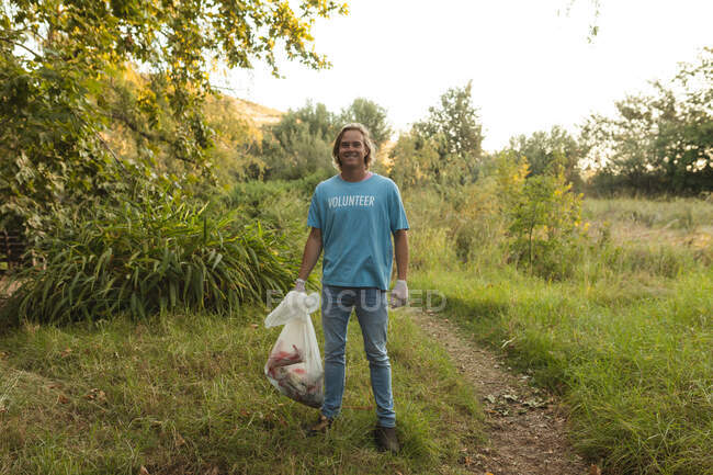 Portrait of happy Caucasian male conservation volunteer cleaning up forest in the countryside, holding rubbish bag, smiling to camera. Ecology and social responsibility in rural environment. — Stock Photo