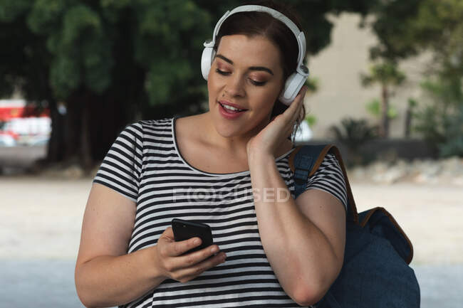 Curvy Caucasian woman out and about in the city streets during the day, smiling and using her smartphone wearing headphones with modern building in the background — Stock Photo
