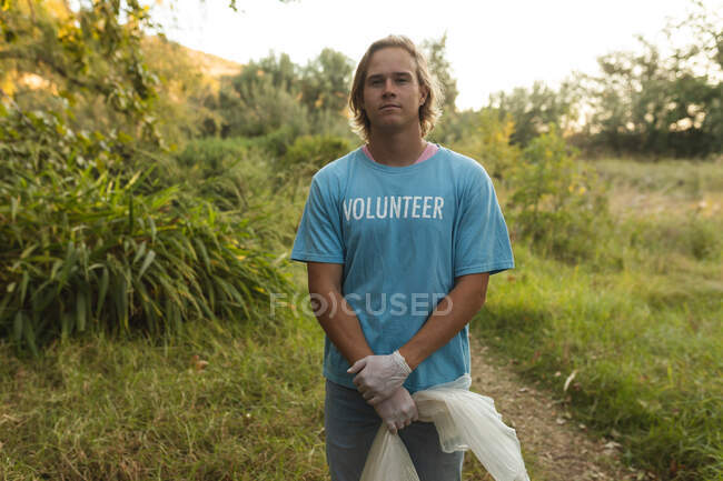 Portrait of happy Caucasian male conservation volunteer cleaning up forest in the countryside, holding rubbish bag looking at camera. Ecology and social responsibility in rural environment. — Stock Photo