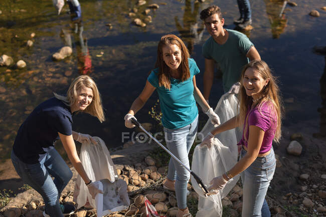 Portrait of happy multi ethnic group of conservation volunteers cleaning up river in the countryside, picking up rubbish smiling to camera. Ecology and social responsibility in rural environment. — Stock Photo