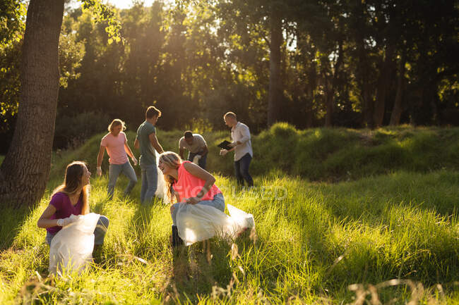 Multi ethnic group of happy conservation volunteers with rubbish bags cleaning up forest in the countryside, picking up rubbish. Ecology and social responsibility in rural environment. — Stock Photo