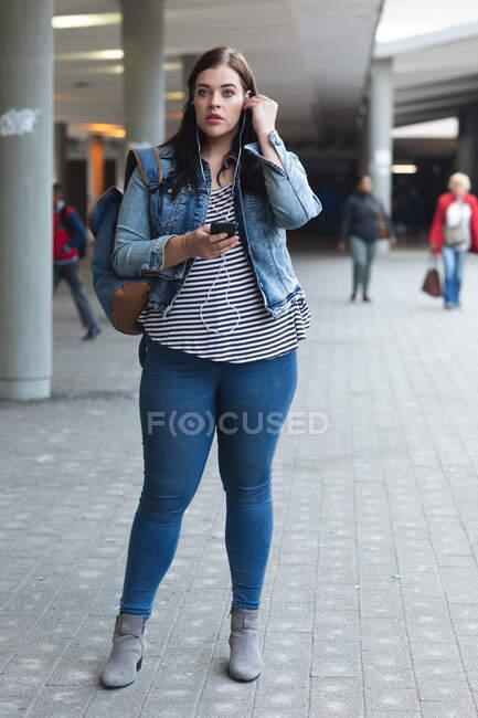Donna caucasica curvy in giro per le strade della città durante il giorno, sorridendo e usando il suo smartphone con gli auricolari, con un edificio moderno sullo sfondo — Foto stock