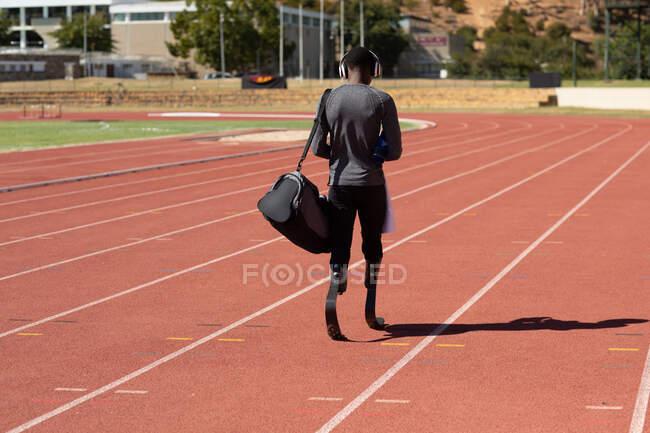 Вид сзади спортсмена с ограниченными физическими возможностями смешанной расы на открытом спортивном стадионе, прогулка с спортивной сумкой на беговой дорожке с беговыми лезвиями. Спортивная подготовка для инвалидов. — стоковое фото