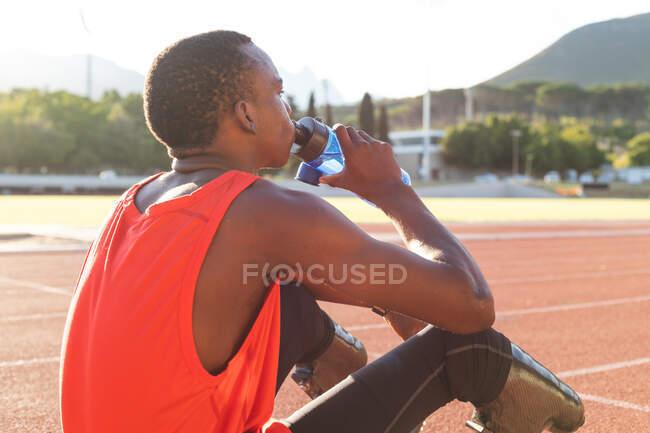 Ajustement, athlète masculin handicapé de race mixte dans un stade de sport de plein air, se reposant et buvant de la bouteille d'eau sur la piste de course portant des lames de course. Handicap athlétisme entraînement sportif. — Photo de stock