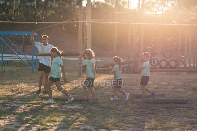 Un entraîneur de fitness masculin caucasien instruisant un groupe de garçons et de filles caucasiens portant des t-shirts verts et des shorts noirs, portant une bûche ensemble sur leurs épaules lors d'un camp d'entraînement par une journée ensoleillée — Photo de stock