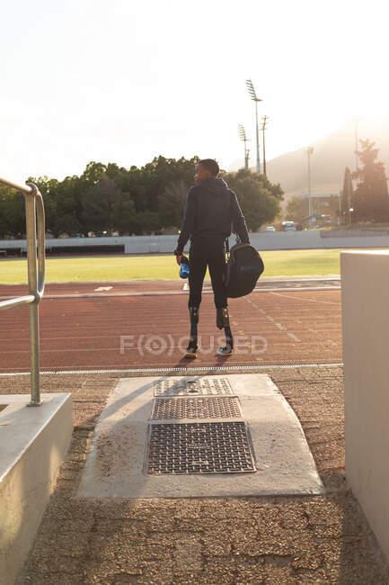 Vue arrière de la forme, athlète masculin handicapé de course mixte dans un stade de sport de plein air, avec sac de sport et bouteille d'eau sur piste de course portant des lames de course. Handicap athlétisme entraînement sportif. — Photo de stock
