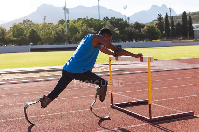 Fit, mixed race disabled male athlete at an outdoor sports stadium, preparing before workout stretching on hurdle on race track wearing running blades. Disability athletics sport training. — Stock Photo