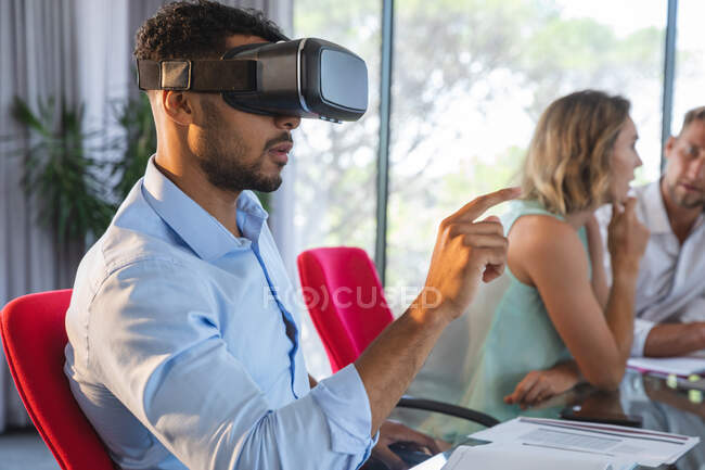 Mixed race businessman sitting at desk using VR headset and virtual 3d interface, with two colleagues discussing in the background. Creative business professionals working in a busy modern office. — Stock Photo