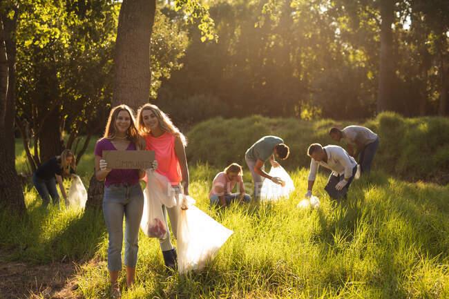 Multi-ethnische Gruppe glücklicher Naturschützer mit Müllsäcken, die den Wald auf dem Land säubern und Müll aufsammeln. Ökologie und soziale Verantwortung im ländlichen Raum. — Stockfoto