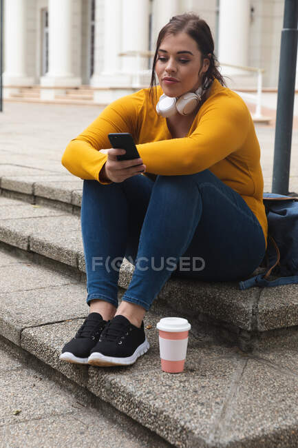 Curvy Caucasian woman out and about in the city streets during the day, sitting on steps with a takeaway coffee, using her smartphone, wearing headphones, with a historical building in the background — Stock Photo