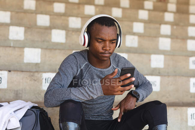 Fit, mixed race disabled male athlete at an outdoor sports stadium, sitting in the stands wearing headphones using smartphone wearing running blades. Disability athletics sport training. — Stock Photo