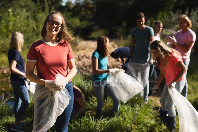 Портрет кавказької жінки - добровольця, що очищає ріку в сільській місцевості, її друзі забирають сміття на задньому плані. Екологія і соціальна відповідальність в сільському середовищі. — Stock Photo