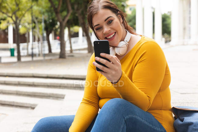 Curvy Caucasian woman out and about in the city streets during the day, sitting on steps, smiling and using her smartphone wearing headphones with a historical building in the background — Stock Photo