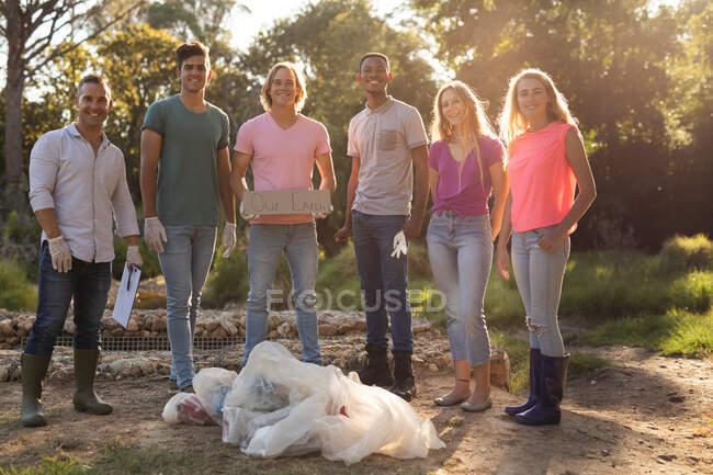 Portrait de plusieurs groupes ethniques de bénévoles heureux de la conservation nettoyant la rivière à la campagne avec bord Notre Terre et des sacs avec des ordures. Écologie et responsabilité sociale en milieu rural. — Photo de stock