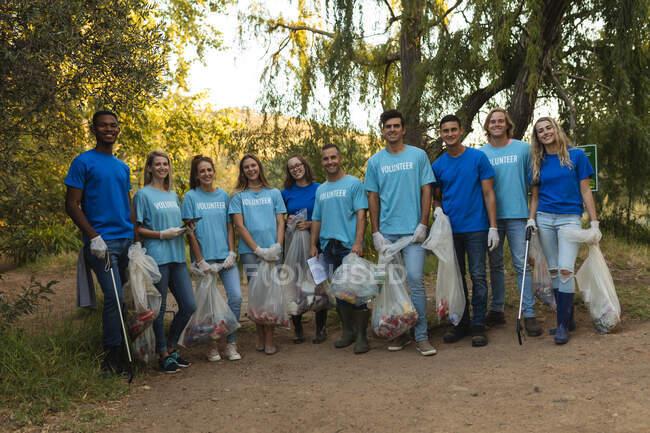 Portrait de plusieurs groupes ethniques de bénévoles de la conservation nettoyant la forêt à la campagne, tenant des sacs remplis d'ordures. Écologie et responsabilité sociale en milieu rural. — Photo de stock