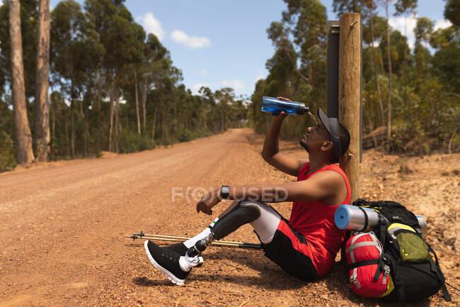 Un atleta maschio di razza mista in forma e disabile con gamba protesica, che si gode il suo tempo durante un viaggio, fa escursioni, si siede su una strada sterrata in un bosco, versa acqua su se stesso. Stile di vita attivo con disabilità. — Foto stock