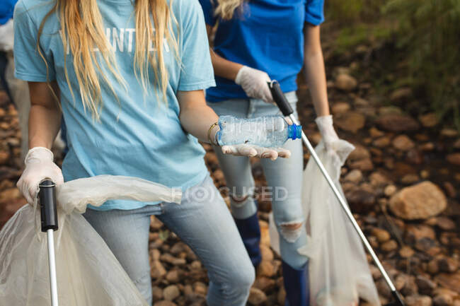 Mid section of female conservation volunteers cleaning up river in the countryside, picking up rubbish holding plastic bottle, refuse sacks. Ecology and social responsibility in rural environment. — Stock Photo