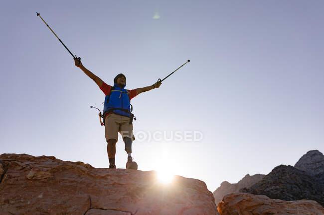 Подтянутый, инвалид смешанной расы спортсмен с протезной ногой, наслаждаясь путешествием в горы, гуляя по скалам с руками над головой с палками. Активный образ жизни с ограниченными возможностями. — стоковое фото