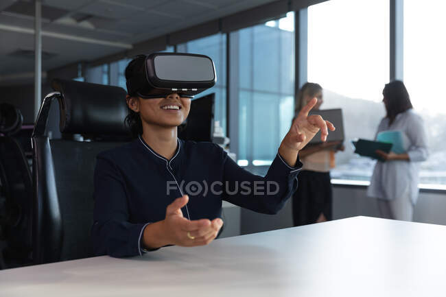 Asian businesswoman working late in the evening in a modern office, sitting at a desk, wearing a vr headset  and touching virtual screen, with her coworkers in the background. — Stock Photo