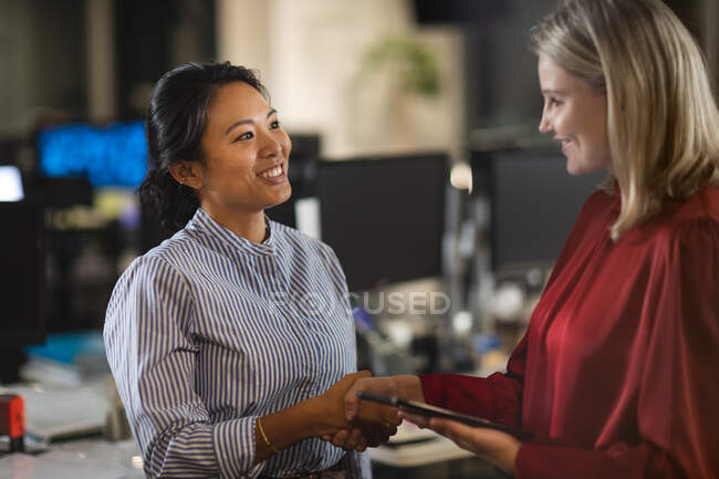 Asian and Caucasian businesswomen working late in the evening in a modern office, using a tablet computer, shaking hands and smiling. — Fotografia de Stock