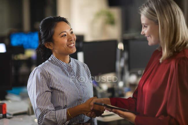 Femmes d'affaires asiatiques et caucasiennes travaillant tard dans la soirée dans un bureau moderne, à l'aide d'un ordinateur tablette, serrant la main et souriant. — Photo de stock