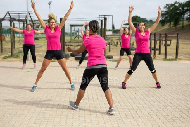 Многонациональная группа женщин носит розовые футболки на тренировочном сборе, занимается спортом, прыгает с парашютом. Открытый групповые упражнения, весело здоровый вызов. — стоковое фото