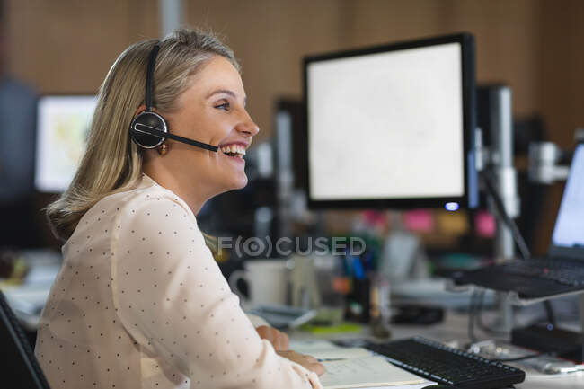 Mulher de negócios caucasiana trabalhando tarde da noite em um escritório moderno, sentada em uma mesa, usando um fone de ouvido, conversando e sorrindo. — Fotografia de Stock