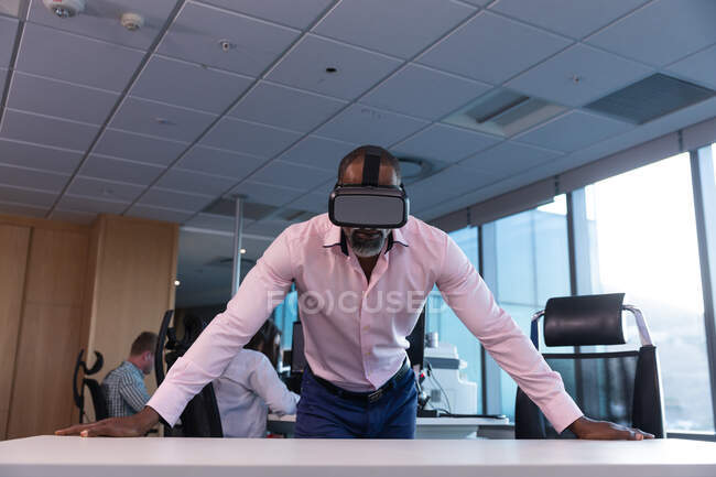 African American businessman working late in the evening in a modern office, leaning on a desk, wearing a vr headset, with his coworkers in the background. — Stock Photo