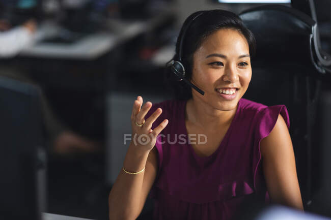 Asian businesswoman working late in the evening in a modern office, sitting at a desk, wearing a phone headset, talking and smiling. — Stock Photo
