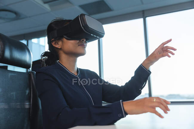 Asian businesswoman working late in the evening in a modern office, sitting at a desk, wearing a vr headset  and touching virtual screen. — Stock Photo