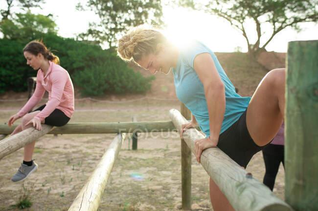 Grupo multiétnico de mujeres todas con camisetas de colores en una sesión de entrenamiento de campo de entrenamiento, ejercicio, bóvedas obstáculos. Ejercicio en grupo al aire libre, divertido desafío saludable. - foto de stock