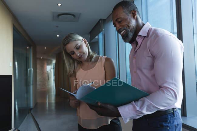 Uomo d'affari afroamericano e donna d'affari caucasica che lavorano fino a tardi la sera in un ufficio moderno, in piedi in un corridoio, discutendo il loro lavoro, guardando i file. — Foto stock