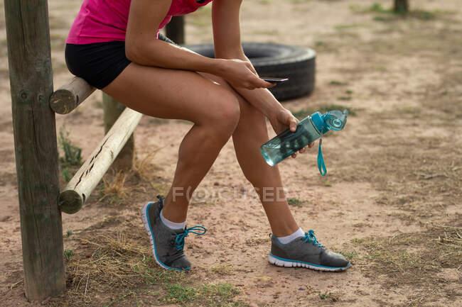 Низкая секция женщины в розовой футболке на тренировке в учебном лагере, упражнения, перерыв, держа бутылку, используя свой смартфон. Открытый групповые упражнения, весело здоровый вызов. — стоковое фото
