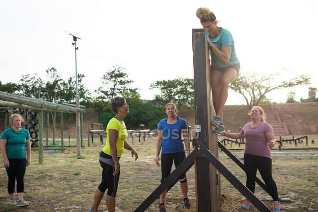Многонациональная группа женщин носит разноцветные футболки на тренировочном сборе, занимается спортом, лезет на стену и аплодирует. Открытый групповые упражнения, весело здоровый вызов. — стоковое фото
