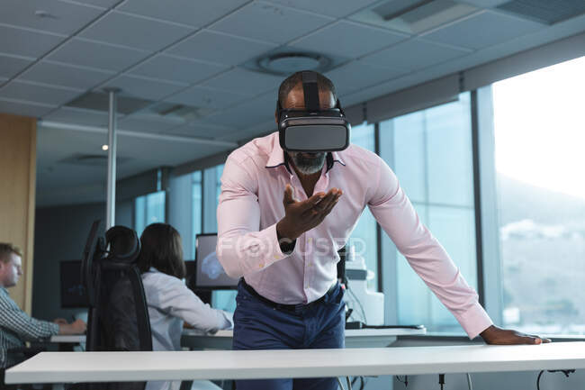 African American businessman working late in the evening in a modern office, leaning on a desk, wearing a vr headset, looking at a virtual screen, with his coworkers in the background. — Stock Photo
