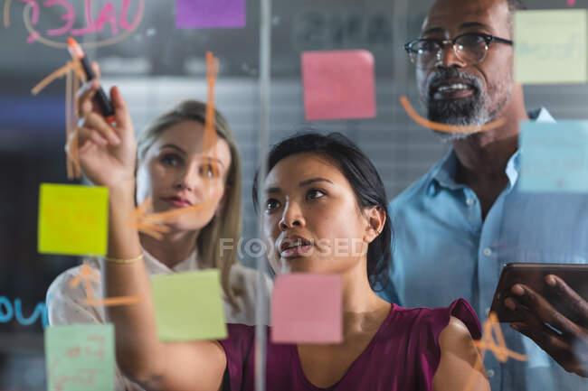 Gruppo multietnico di colleghi che lavorano fino a tardi la sera in un ufficio moderno, scrivendo su un moodboard di vetro e brainstorming. — Foto stock
