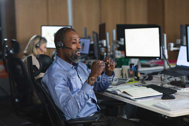 African American businessman working late in the evening in a modern office, sitting at a desk, wearing a phone headset and talking. — Stock Photo