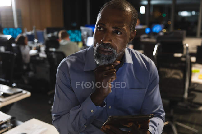 Hombre de negocios afroamericano que trabaja hasta tarde en la noche en una oficina moderna, sentado en un escritorio, usando una tableta, sosteniendo su barbilla y pensando. - foto de stock