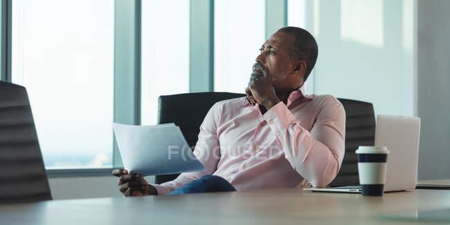 Афроамериканский бизнесмен, работающий допоздна в современном офисе, сидящий за столом, держащий листок бумаги и думающий:. — стоковое фото