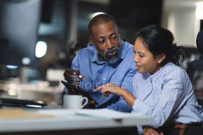 Asian businesswoman and African American businessman working late in the evening in a modern office, sitting at a desk, using a tablet computer and discussing their work. — Fotografia de Stock
