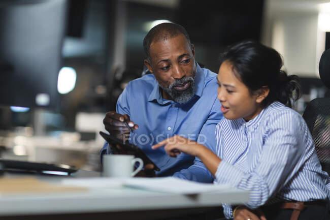 Азійська комерсантка і афроамериканський бізнесмен працюють пізно ввечері в сучасному офісі, сидячи за столом, використовуючи планшетний комп'ютер і обговорюючи свою роботу.. — стокове фото