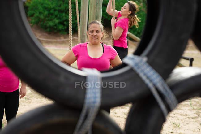 Смешанная расовая женщина в розовой футболке на тренировке в учебном лагере, упражнения, взгляд на камеру, групповое лазание по веревке на заднем плане. Открытый групповые упражнения, весело здоровый вызов. — стоковое фото