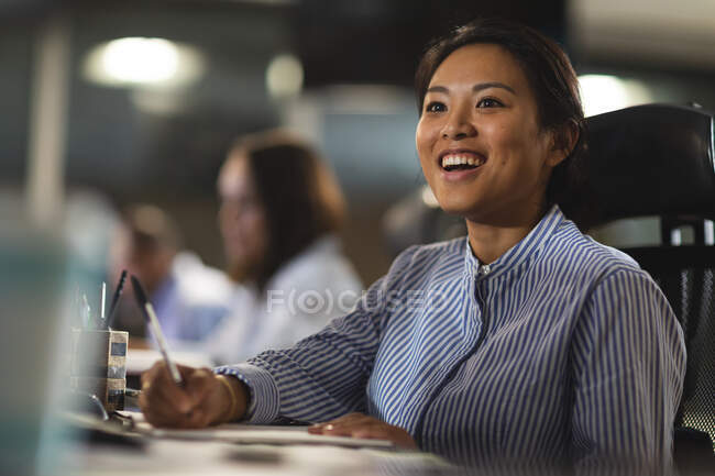 Asian businesswoman working late in the evening in a modern office, sitting at a desk, taking notes and smiling, with her coworkers in the background. — Stock Photo