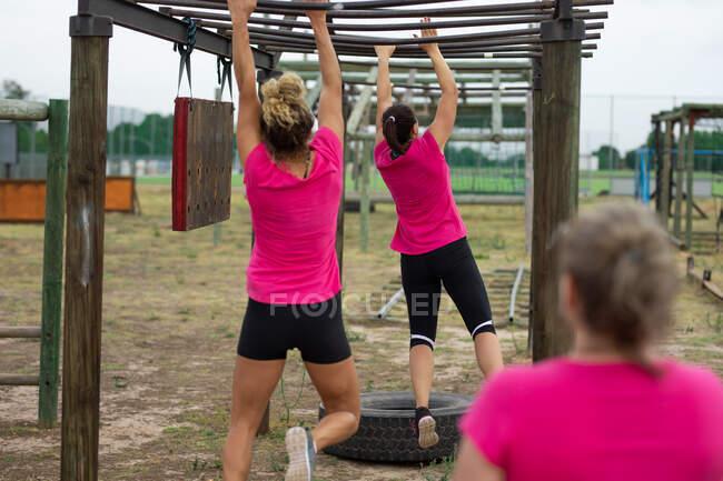 Groupe multiethnique de femmes portant toutes des t-shirts roses lors d'une séance d'entraînement au camp d'entraînement, faisant de l'exercice, suspendues à des barres de singe. Exercice de groupe en plein air, défi sain amusant. — Photo de stock