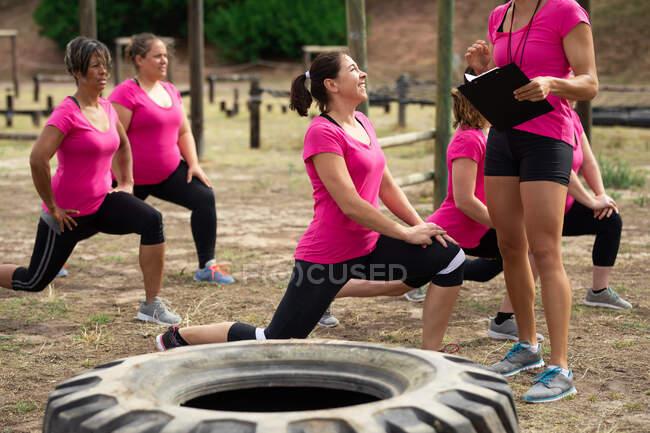 Многонациональная группа женщин носит розовые футболки на тренировочном сборе, занимается спортом, разминает ноги и мотивирует диван. Открытый групповые упражнения, весело здоровый вызов. — стоковое фото