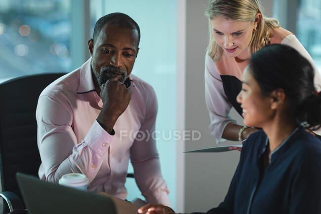 Gruppo multietnico di colleghi che lavorano fino a tarda sera in un ufficio moderno, seduti alla scrivania, utilizzando un computer portatile e discutendo del loro lavoro. — Foto stock