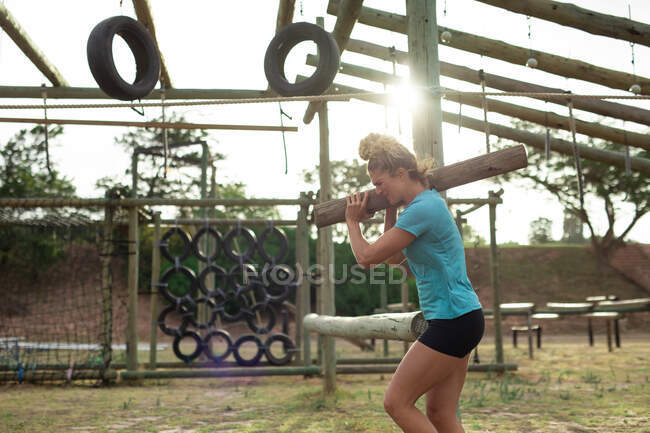 A fit Caucasian woman wearing blue t shirt at a boot camp training session, exercising, carrying a log. Outdoor group exercise, fun healthy challenge. — Stock Photo