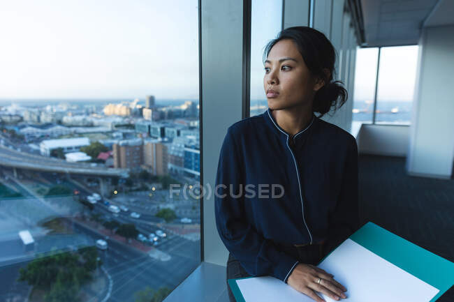 Asian businesswoman working late in the evening in a modern office, holding a folder, looking through a window and thinking. — Stock Photo