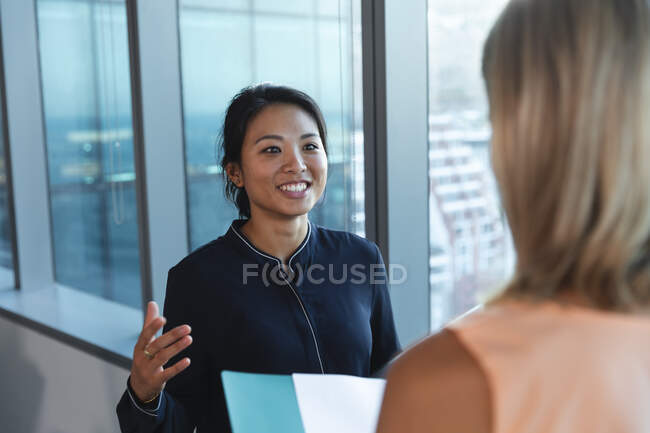 Asian and Caucasian businesswomen working late in the evening in a modern office, standing next to a window and discussing their work. — Fotografia de Stock